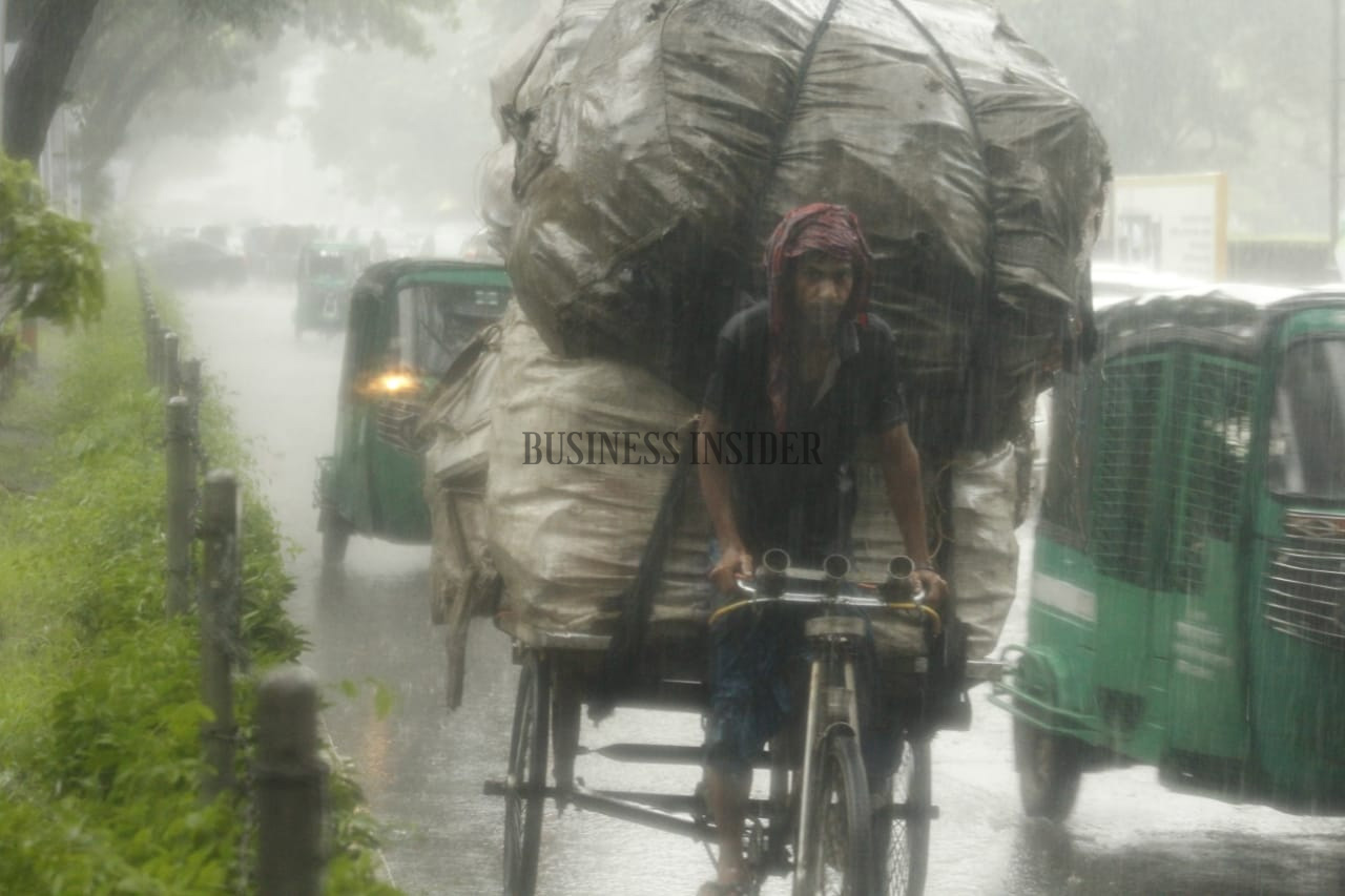 A van puller is seen on the raod without any umbrella or rain-coat
