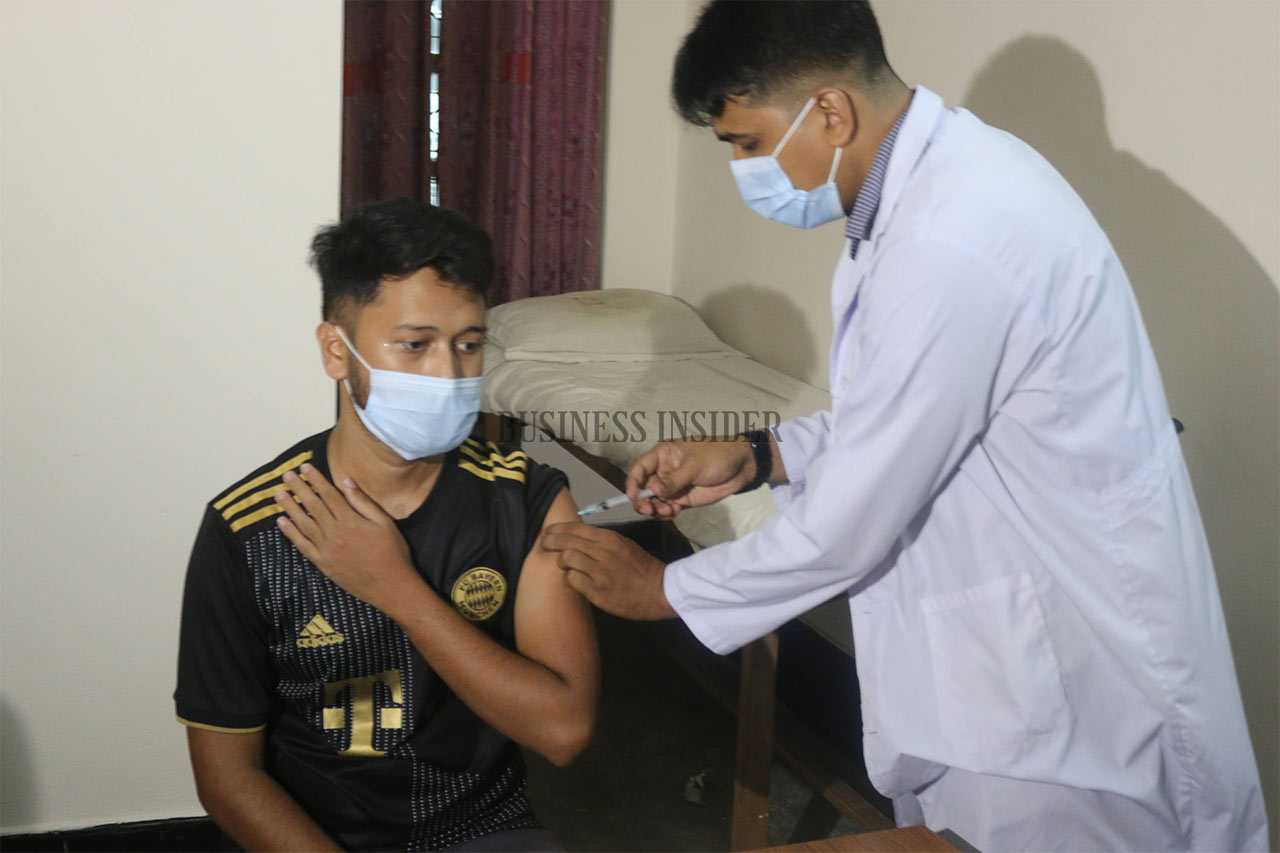 A health official injects a student with the vaccine
