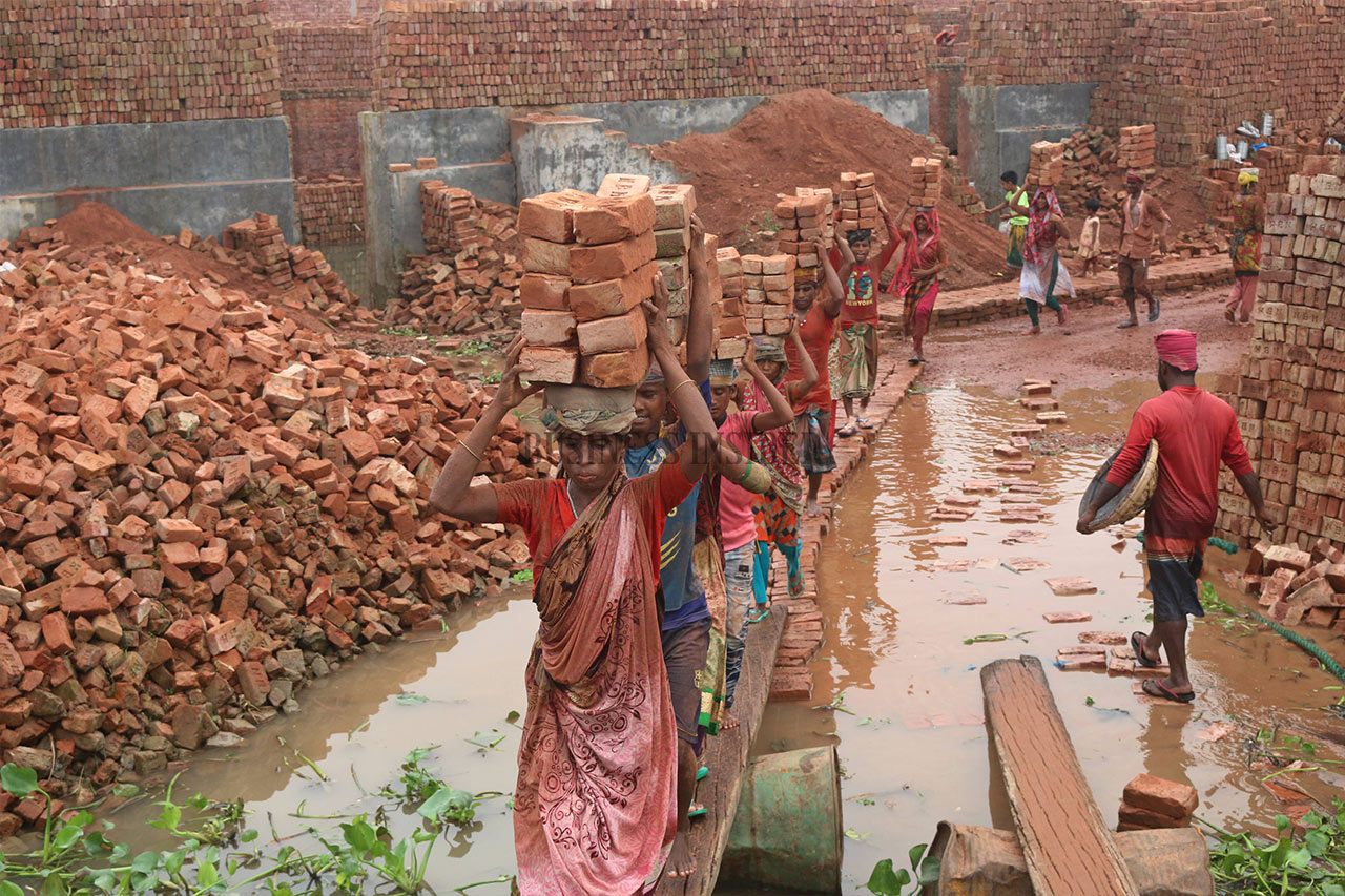 Workers carry stacks of bricks on their heads