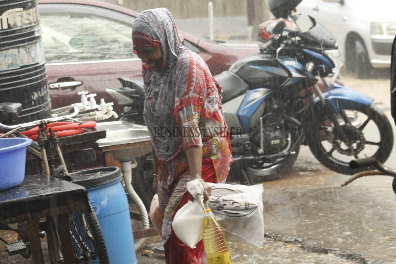 A woman on the way to her home after taking some grocery items in the rain