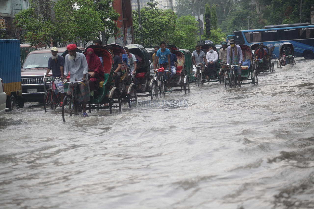 Rickshaws and other vehicles pull through the water