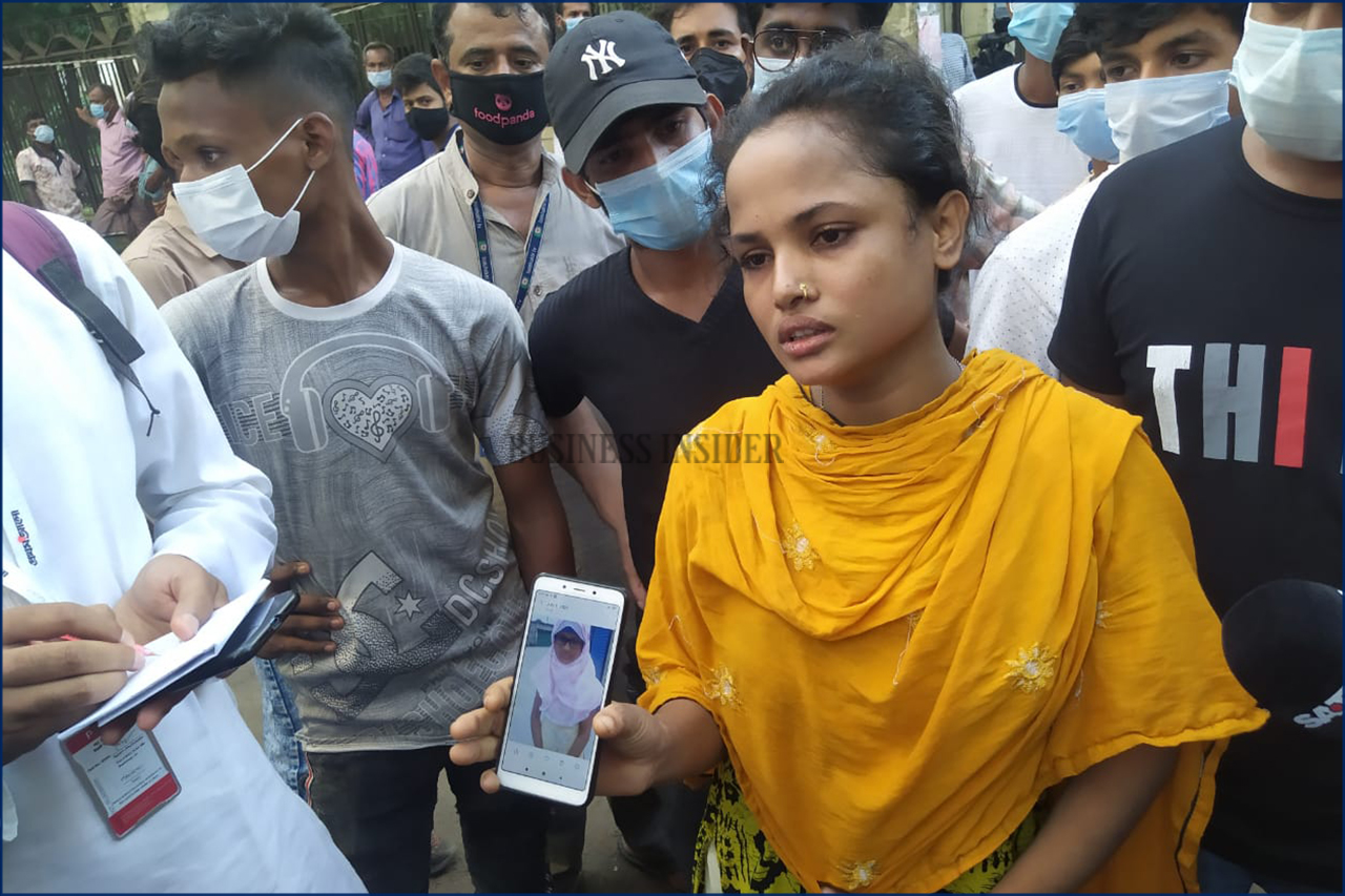 A girl shows a photo of her missing relative on mobile screen