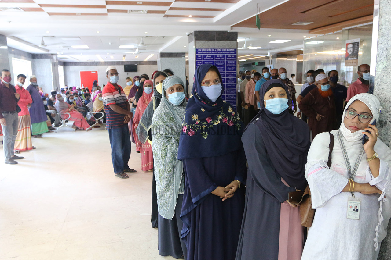 Women stand in a separate line to take vaccine shots