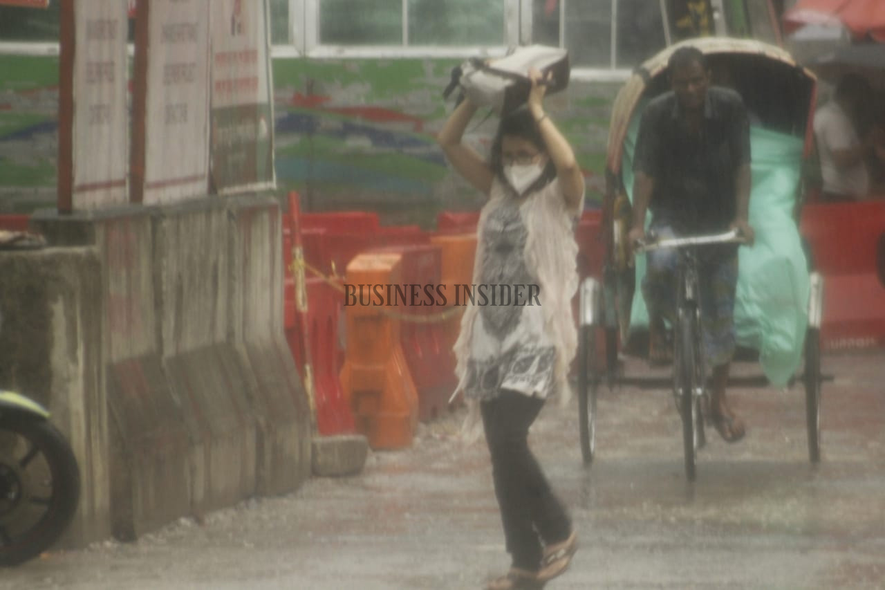 A woman holds her bag above her head to save herself from the rainfall
