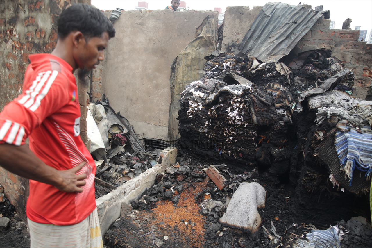 A man looks at the debris from the fire