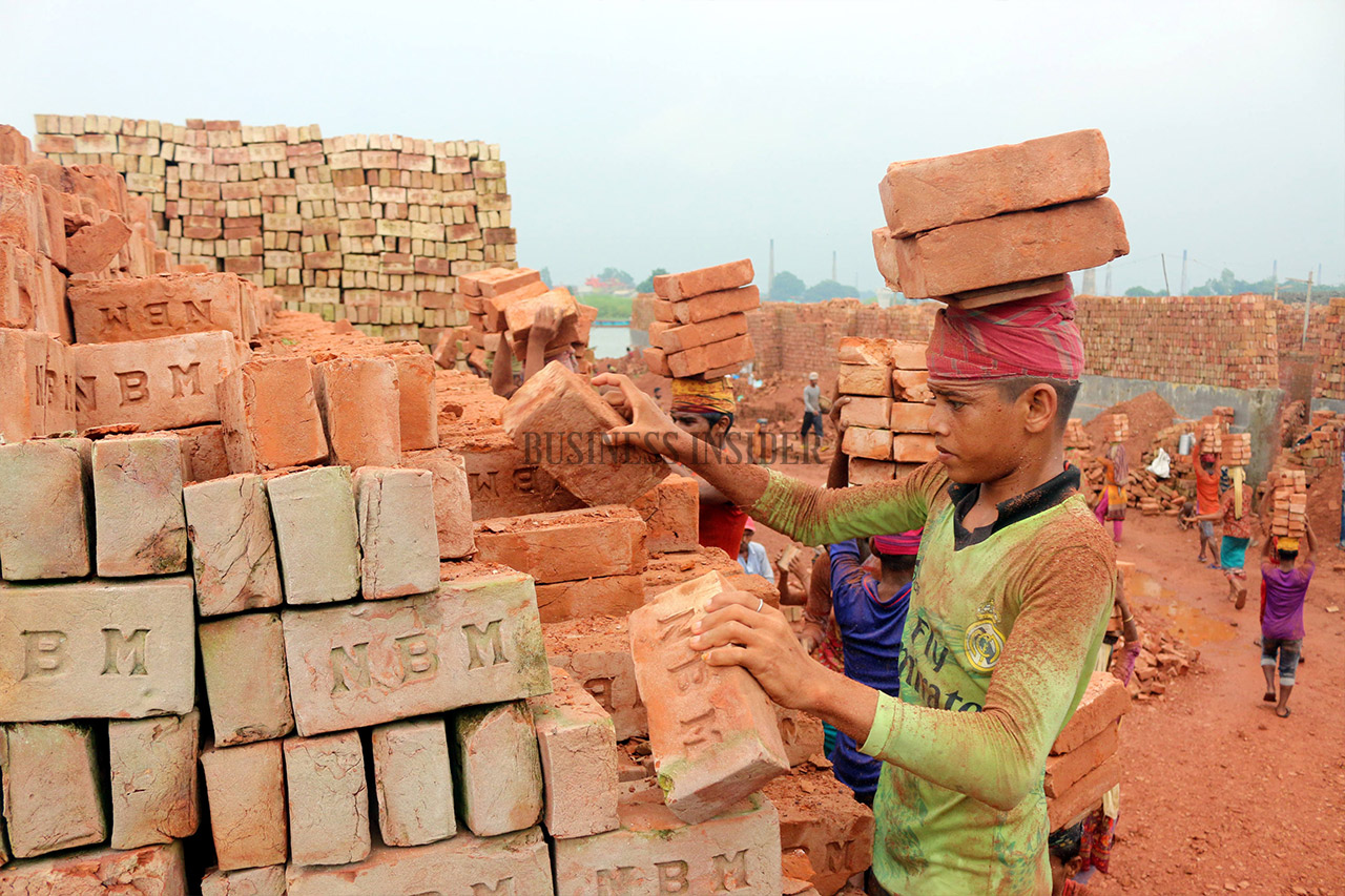 A child worker stacking bricks on his head