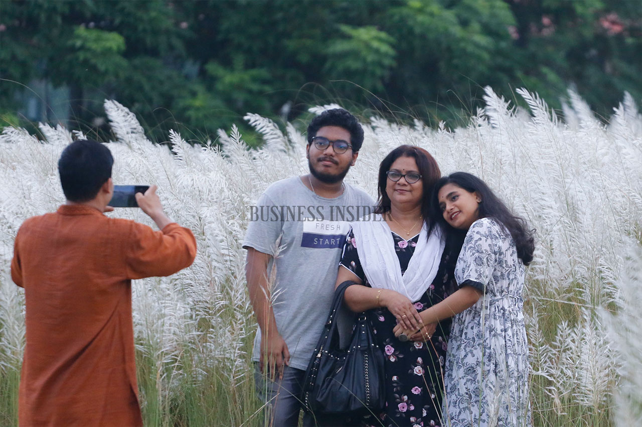 A family takes photo amid the Kashful flowers.
