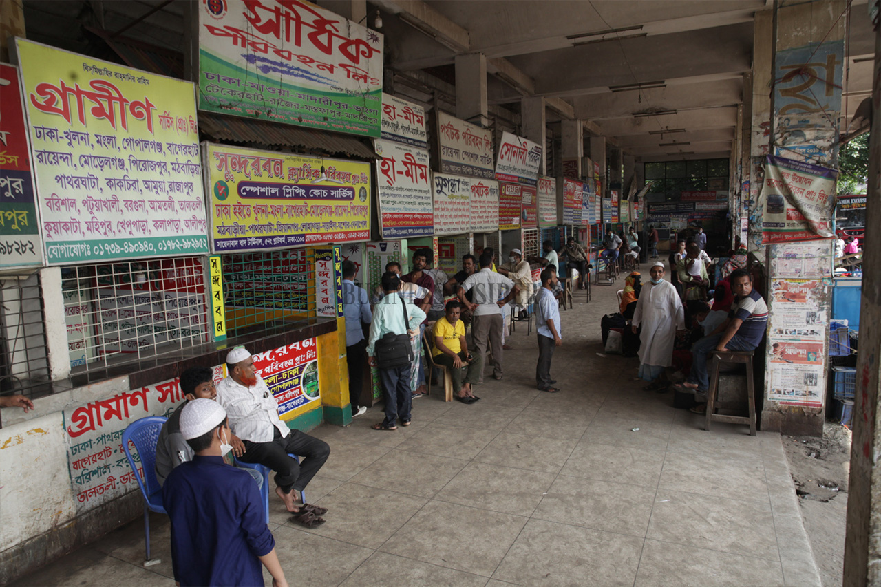 People are buying tickets at a Dhaka counter