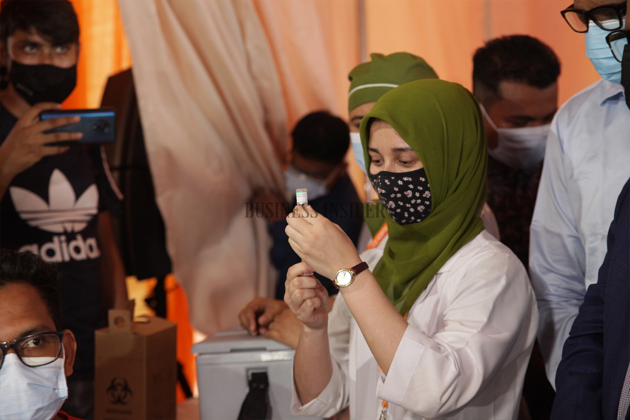 A health worker injects a syringe into a vial