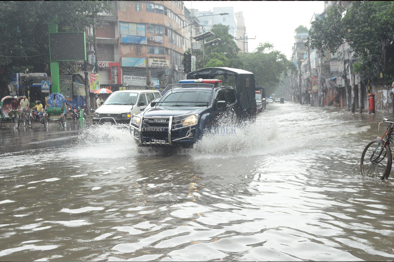 A car speeds in the waterlogged road