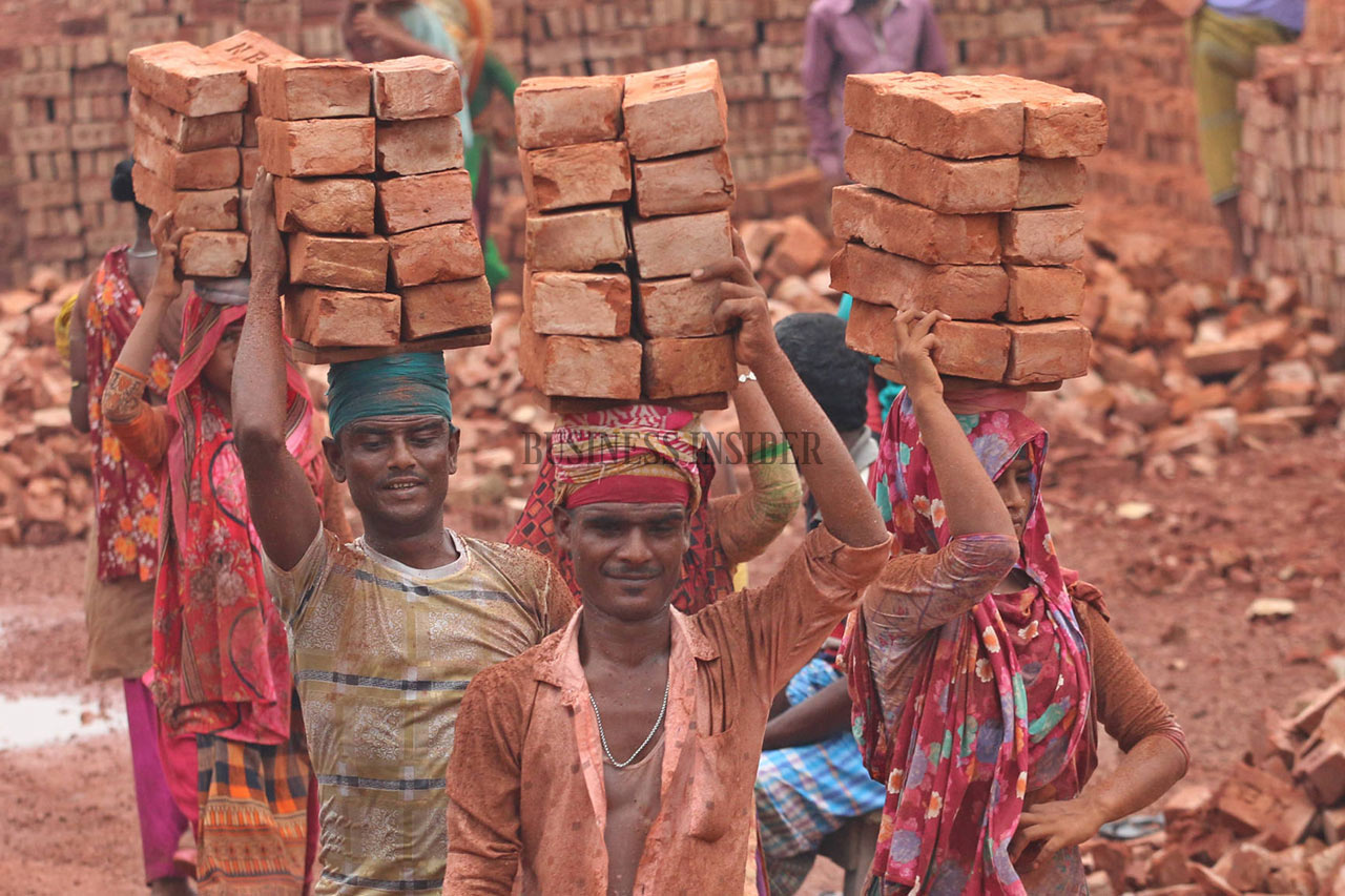 Workers balance bricks on top of their heads