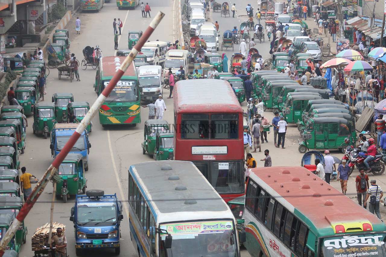 Cars, buses and CNG pass a signal